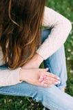 有拿着苹果树的中立修指甲的女性手变粉红色花 户外,春天 免版税库存照片
