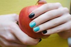 有拿着苹果的黑修指甲的女性手 免版税库存图片