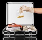 有拿着药物的美元、手枪和手的手提箱被隔绝 免版税库存照片