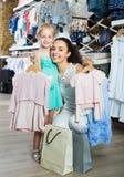有拿着衣裳的女儿的妇女在孩子商店 库存照片