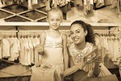 有拿着衣裳的小女孩的年轻快乐的妇女 库存照片