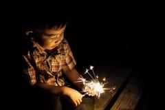 有拿着闪烁发光物的一张滑稽的面孔的逗人喜爱的小男孩 图象与 库存照片