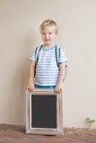 有拿着黑板的背包的一个愉快的年轻男孩反对a 图库摄影