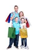 有拿着购物袋的孩子的愉快的美国家庭 免版税库存图片