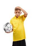 有拿着他的头的足球的严肃,迷茫的男孩被隔绝在白色背景 学校活动概念 免版税库存图片