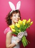 有拿着黄色郁金香的兔宝宝耳朵的妇女 库存图片