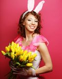 有拿着黄色郁金香的兔宝宝耳朵的妇女 免版税库存照片
