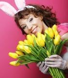 有拿着黄色郁金香的兔宝宝耳朵的妇女 免版税库存图片