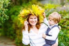 有拿着autu的枫叶花圈的母亲小小孩男孩 免版税库存图片