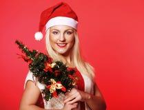有拿着christmass树的圣诞老人帽子的妇女 免版税库存照片