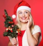 有拿着christmass树的圣诞老人帽子的妇女 免版税库存图片