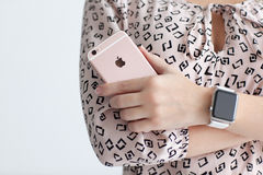 有拿着iPhone 6 S罗斯金子的苹果计算机手表的妇女 库存照片