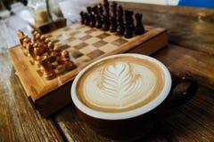 有拿铁艺术和棋枰的咖啡杯 免版税库存图片