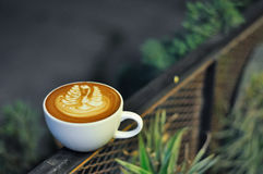 有拿铁艺术的咖啡杯在金属篱芭在晚上 免版税库存图片