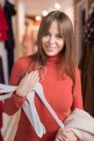 有挂衣架的女孩在商店 图库摄影