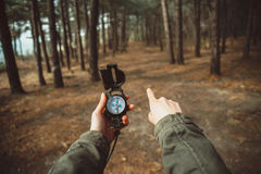 有指南针指向的方向的远足者在森林里 库存照片