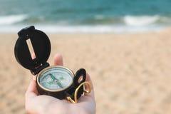 有指南针的女性手在海洋背景 免版税库存图片