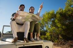 有指向在有轮胎的公路车辆的人的妇女 免版税图库摄影
