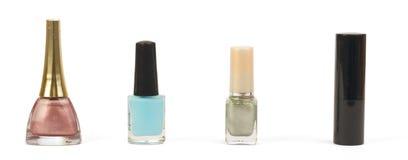 有指甲油和唇膏的瓶在白色 免版税库存图片