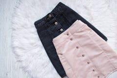 有按钮的黑和桃红色牛仔布裙子 时兴的概念,在白色毛皮背景 图库摄影