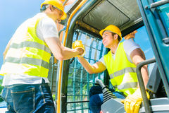 有挖掘机的两名亚裔工作者在建造场所 免版税库存图片