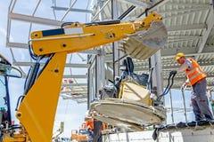 有挖掘机的移动的力量修平刀机器在一个新的工作站点 库存照片