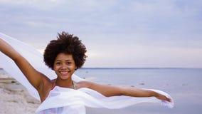 有挥动在海滩的风的披肩的非洲妇女 影视素材