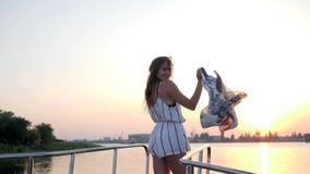 有挥动的布料的女性到在风帆弓的手里在夏天周末在背景日落的海 股票录像