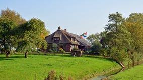 有挥动的旗子的农舍农场在Jukwerd,格罗宁根 免版税库存照片