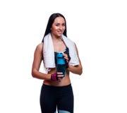 有振动器和毛巾的健身女孩在白色背景 放松在锻炼以后的可爱的运动妇女 免版税库存图片