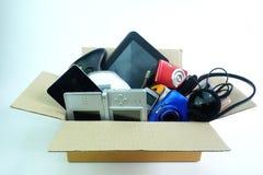 有损坏的或老使用的电子小配件的纸箱为在白色背景的每日使用 免版税库存图片