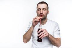 有捷径的一个人通过秸杆喝着从瓶的焦炭 这个人喜欢吃快餐和喝甜点 库存照片