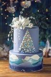 有排列的蛋糕与一束圣诞树和白花的图象的蓝色蛋糕在上面 欢乐点心的概念 免版税库存照片