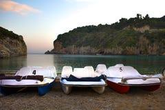 有排队沿岸的被折叠的机盖的三条脚蹬小船 站立在海滩前附近的两峭壁 粗糙的沙子和 库存图片