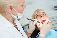 有探针的牙医审查的病人 免版税图库摄影