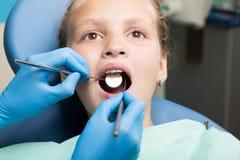 有接受牙齿治疗的开放嘴的愉快的小女孩在诊所 被检查和治疗牙的牙医孩子 免版税库存图片