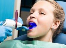 有接受牙齿治疗的开放嘴的愉快的小女孩在诊所 被检查和治疗牙的牙医孩子 免版税库存照片