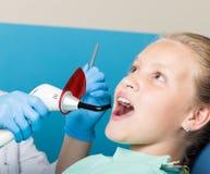 有接受牙齿治疗的开放嘴的愉快的小女孩在诊所 被检查和治疗牙的牙医孩子 免版税图库摄影