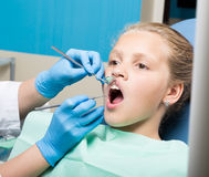 有接受牙齿治疗的开放嘴的愉快的小女孩在诊所 被检查和治疗牙的牙医孩子 图库摄影