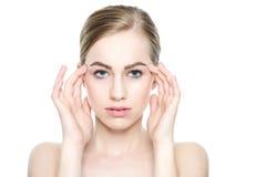 有接触她的面孔的完善的皮肤的美丽的年轻白肤金发的妇女 面部治疗 整容术、秀丽和温泉概念 免版税库存照片