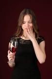 有接触她的面孔的葡萄酒杯的女孩 关闭 深红的背景 免版税图库摄影