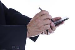 有接触智能手机的屏幕铁笔的手 免版税库存照片