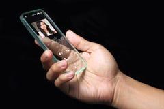 有接踵而来的录影电话象的男性手在智能手机屏幕上 免版税库存照片