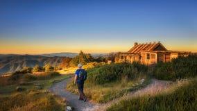 有接近一个小屋的背包的年轻远足者在澳大利亚 免版税图库摄影