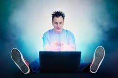 有控制杆的滑稽的人坐在膝上型计算机前面的地板 游戏玩家戏剧 免版税库存图片
