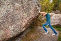 有推挤一块巨大的石头的背包的人 免版税库存图片