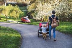 有推挤一辆跑步的婴儿推车外面在春天自然的小孩儿子的一个父亲 免版税库存图片