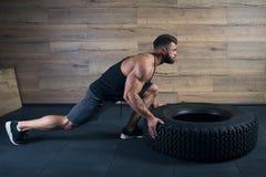 有推挤在黑无袖衫和灰色短裤的胡子的肌肉人一个轮胎在健身房 库存照片