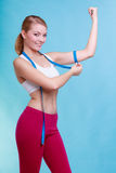 有措施卷尺的健身妇女适合的女孩她的二头肌 库存图片