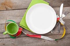 有措施磁带、杯子、刀子和叉子的板材 在woode的饮食食物 免版税库存照片